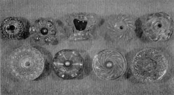 Eight Designs of American Cast Knobs: All are of clear glass. Top row, left to right: Ribbed mushroom design; hollow rosette type and broken knob of same design showing hollow center; swirled mushroom; and design imitating cut glass. Lower row, left to right: Design of fine diamond shapes surrounding deep central cup; hollow crown-shaped rosette; swirl ribs on flat face and conventionalized floral design, also found on Sandwich glass tiebacks.